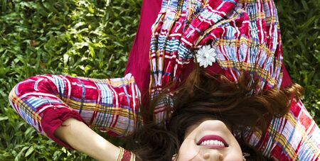 Indian woman is lying on the green grass