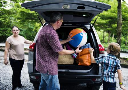 Família caucasiana com carro tronco aberto no parque de estacionamento