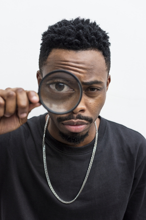 African man playing with a magnifying glass Reklamní fotografie - 94913181