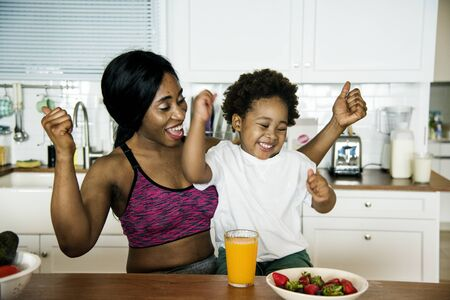 Mother and son eating healthy food in the kitchen
