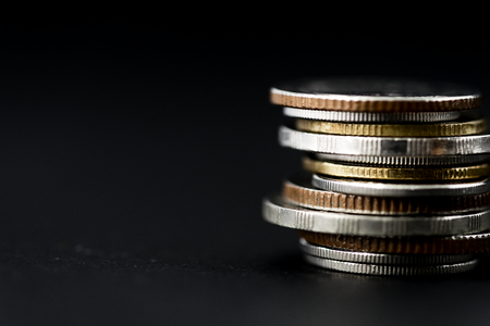 Closeup of coins stack isolated on black background