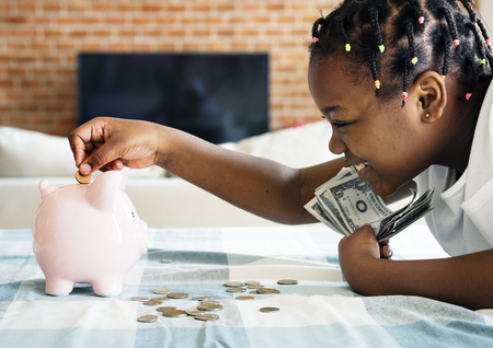 Black girl collecting money to piggy bank