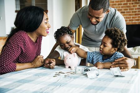 Family saving money to piggy bank