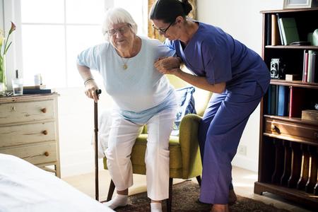 シニア女性が立つのを助ける看護師