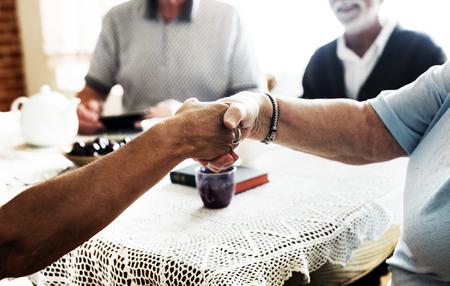 Casual seniors shaking hands