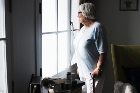 自宅で一人で立っているシニア女性