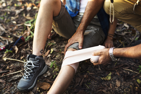 Man putting bandage on his partner's knee in the jungle