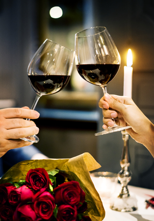 Couple holding wineglasses and clinking