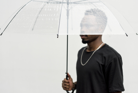 African man using an umbrella Reklamní fotografie - 94851213