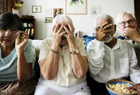 Senior vrienden zittend op de bank met gruwelijke reactie Stockfoto