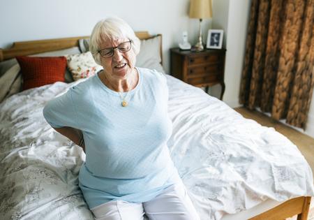 Ltere Frau , die auf dem Bett in den Schmerz sitzt Standard-Bild - 94671481