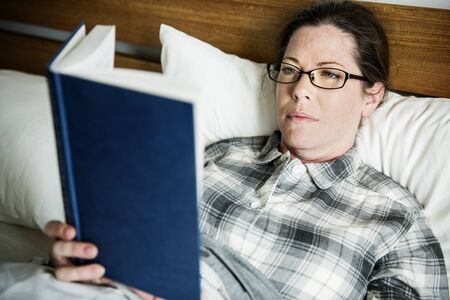 A woman reading in bed Stock Photo