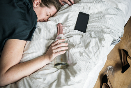 A drunk woman passig out in bed Stock Photo - 95111330