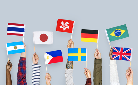 Hands holding various country flags Stockfoto