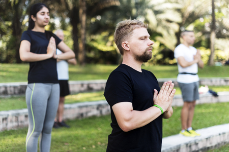 People doing yoga at the park Imagens