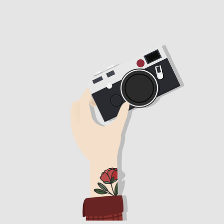 Hand with tattoos holding a camera