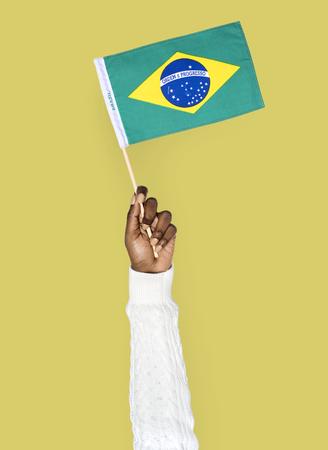 Hand holding a Brazilian flag