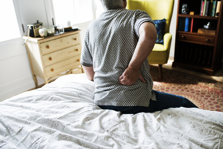 Senior man sitting on the bed in pain Stockfoto
