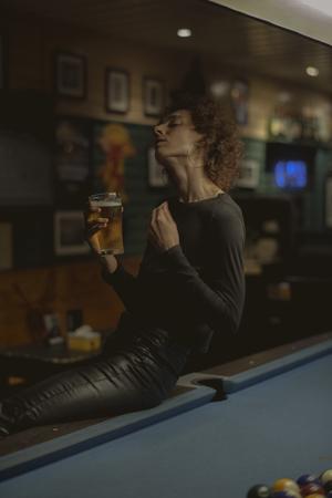 Woman having a beer at a bar Фото со стока