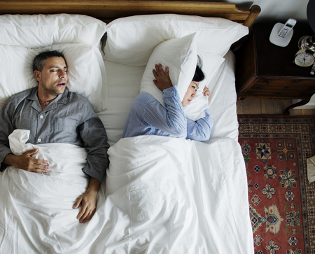 Interracial couple on the bed man snoring and disrupting woman Standard-Bild