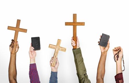 Manos sosteniendo cruces y biblias