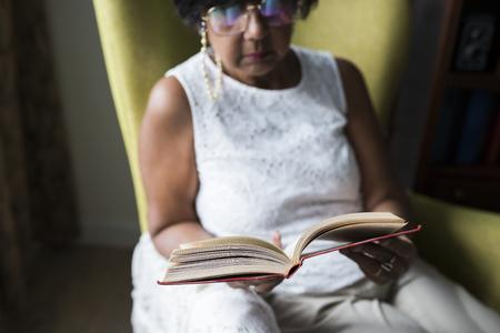 Ltere Frau liest Buch im Zimmer Standard-Bild - 95112535