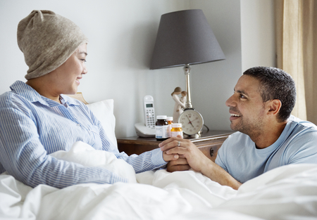A sick woman in bed with her partner Stockfoto