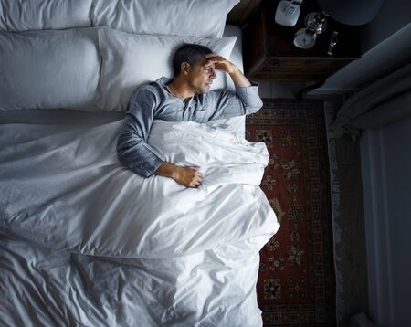 Man on bed with a headache 版權商用圖片 - 95112548