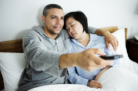 A couple watching tv together in bed