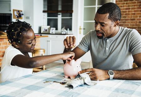 Dad and daughter saving money to piggy bank Фото со стока - 95112778