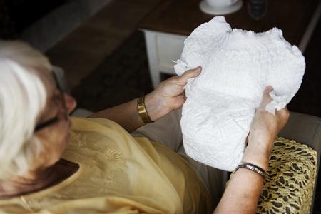 Ältere Frau , die eine Windel betrachtet