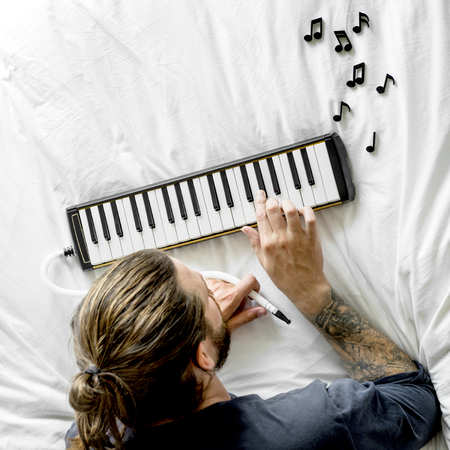 Man lying on bed and using a melodica Stok Fotoğraf