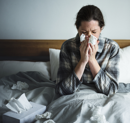 A woman suffering from flu in bed 版權商用圖片