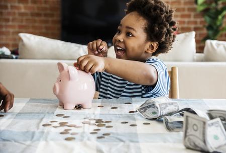 Black boy collecting money to piggy bank 스톡 콘텐츠