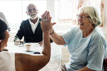 Senior women giving each other high five Stock Photo