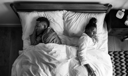 African American couple sleeping back to back