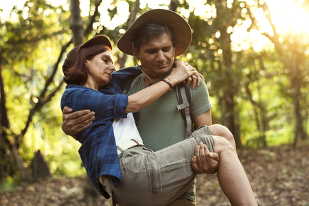 Man holding his partner up while trekking in the jungle Stock Photo