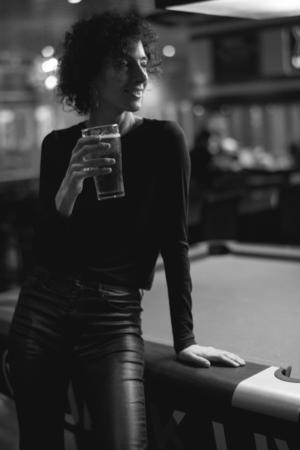 Woman having a beer at a bar Stock Photo