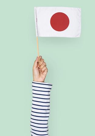 Hand holding a Japanese flag