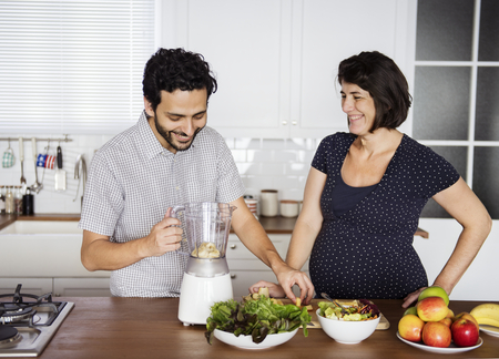 Caucasian couple making fresh smoothie Banco de Imagens