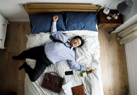 Drunk Asian business man falling asleep as soon as he came back home Stock Photo - 95182166