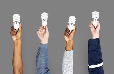 People holding energy saving bulbs Фото со стока