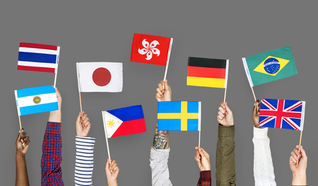 Hands holding international flags Stock Photo