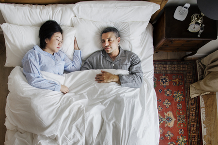 Interracial couple sleeping together on the bed 写真素材