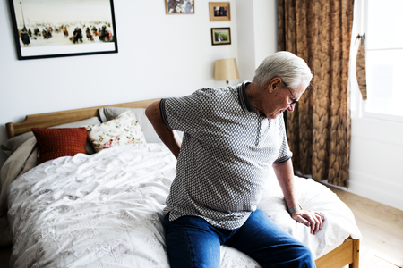 Senior man sitting on the bed in pain Stock Photo