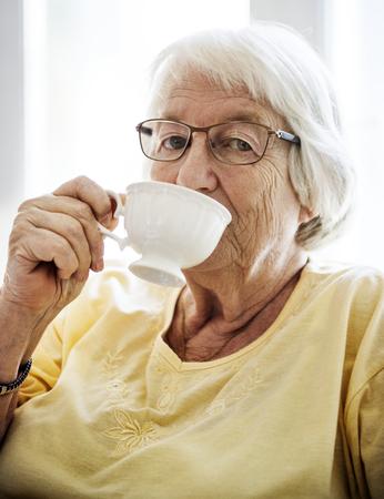 カメラを見ながらお茶をすする先輩女性 写真素材
