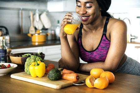 黒人女性はオレンジジュースを飲んでいる 写真素材
