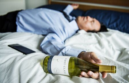 A drunk businessman passing out in bed