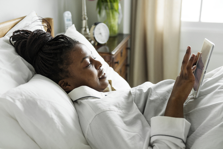 A woman using a phone in bed