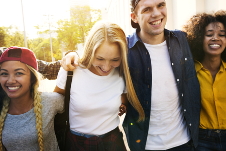 Smiling happy young adult friends arms around shoulder walking outdoors Stock Photo